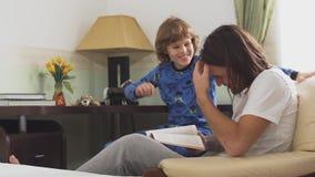 Δύο αδελφοί που κάθονται στην καρέκλα βραχιόνων, παλαιότερος αδελφός διαβάζουν για το μικρό αδελφό ένα βιβλίο και ένα νέο αγόρι σ φιλμ μικρού μήκους