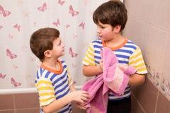 Δύο αδελφοί που σκουπίζουν μαζί με τη ρόδινη πετσέτα στο λουτρό Στοκ εικόνα με δικαίωμα ελεύθερης χρήσης