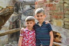 Δύο αδελφοί στέκονται κοντά στο σπίτι, την έννοια της φυσικής καταστροφής, την πυρκαγιά, και την ερήμωση στοκ εικόνες