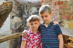 Δύο αδελφοί στέκονται κοντά στο σπίτι, την έννοια της φυσικής καταστροφής, την πυρκαγιά, και την ερήμωση στοκ φωτογραφίες με δικαίωμα ελεύθερης χρήσης