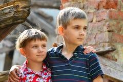 Δύο αδελφοί στέκονται κοντά στο σπίτι, την έννοια της φυσικής καταστροφής, την πυρκαγιά, και την ερήμωση στοκ φωτογραφία