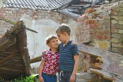 Δύο αδελφοί στέκονται κοντά στο σπίτι, την έννοια της φυσικής καταστροφής, την πυρκαγιά, και την ερήμωση στοκ εικόνες με δικαίωμα ελεύθερης χρήσης