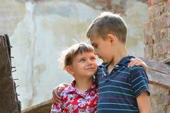 Δύο αδελφοί στέκονται κοντά στο σπίτι, την έννοια της φυσικής καταστροφής, την πυρκαγιά, και την ερήμωση στοκ φωτογραφία με δικαίωμα ελεύθερης χρήσης