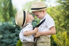 Δύο αδελφοί στα καπέλα αχύρου που παίζουν και που έχουν τη διασκέδαση στοκ φωτογραφία
