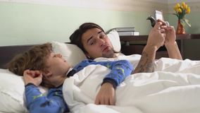 Δύο αδελφοί στις πυτζάμες που βρίσκονται στο κρεβάτι στην κρεβατοκάμαρα το πρωί Ο παλαιότερος αδελφός στο τηλέφωνο κυττάρων ενώ απόθεμα βίντεο