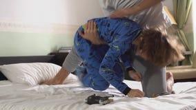 Δύο αδελφοί στις πυτζάμες που παλεύουν το παιχνίδι και που γύρω στο κρεβάτι στην κρεβατοκάμαρα το πρωί παλαιότερος νεώτερος απόθεμα βίντεο