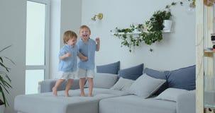 Δύο αδελφοί των μικρών παιδιών πηδούν στον καναπέ και έχουν τη διασκέδαση Χαρά, γέλιο και διασκέδαση στο σπίτι E φιλμ μικρού μήκους