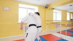 Δύο αθλητικά άτομα που εκπαιδεύουν τις δεξιότητες aikido τους στο στούντιο Parries το χτύπημα και ρίψη του αντιπάλου στο πάτωμα φιλμ μικρού μήκους