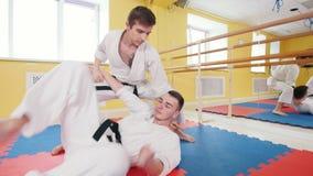 Δύο αθλητικά άτομα που εκπαιδεύουν τις δεξιότητες aikido τους Parries το χτύπημα και ρίψη του αντιπάλου στο πάτωμα φιλμ μικρού μήκους