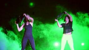 Δύο αθλητικά, όμορφος, γυναίκες που κάνουν τις ασκήσεις δύναμης με τα βαρέων βαρών πιάτα, τη νύχτα, στον ελαφρύ καπνό, ομίχλη, μέ φιλμ μικρού μήκους