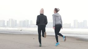 Δύο αθλητικές γυναίκες που στέκονται στην παραλία και που θερμαίνουν για το τρέξιμο Κρύος καιρός απόθεμα βίντεο