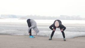 Δύο αθλητικές γυναίκες που στέκονται στην παραλία και το ζέσταμα Κρύος καιρός απόθεμα βίντεο