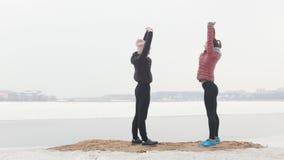 Δύο αθλητικές γυναίκες που τρέχουν σε μια χιονώδη παραλία Στάση στο έδαφος και τράβηγμα των χεριών τους επάνω φιλμ μικρού μήκους