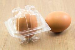 Δύο ακατέργαστα αυγά στο πλαστικό κιβώτιο στον ξύλινο πίνακα Στοκ Εικόνες