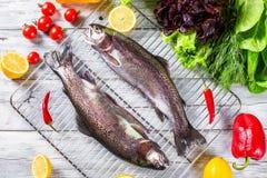 Δύο ακατέργαστα ψάρια πεστροφών με τις φέτες λεμονιών, καυτά πιπέρια, ντομάτες Στοκ Εικόνες