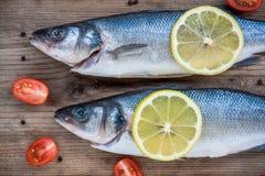 Δύο ακατέργαστα seabass ψάρια με τις ντομάτες λεμονιών και κερασιών στο ξύλινο BA Στοκ Εικόνες