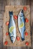 Δύο ακατέργαστα seabass ψάρια με τις ντομάτες λεμονιών φετών και κερασιών στο W Στοκ Εικόνες