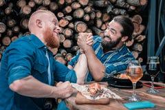 Δύο ακτινοβολώντας ώριμα άτομα που έχουν τη διασκέδαση πίνοντας την μπύρα στοκ εικόνες