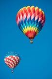Δύο λαμπρά χρωματισμένα μπαλόνια ζεστού αέρα με ένα μπλε υπόβαθρο ουρανού Στοκ φωτογραφία με δικαίωμα ελεύθερης χρήσης
