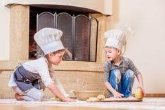 Δύο αμφιθαλείς - αγόρι και κορίτσι - στα καπέλα αρχιμαγείρων ` s κοντά στη συνεδρίαση εστιών στο πάτωμα κουζινών που λερώνεται με Στοκ εικόνες με δικαίωμα ελεύθερης χρήσης