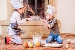 Δύο αμφιθαλείς - αγόρι και κορίτσι - στα καπέλα αρχιμαγείρων ` s κοντά στη συνεδρίαση εστιών στο πάτωμα κουζινών που λερώνεται με Στοκ Εικόνες
