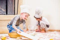 Δύο αμφιθαλείς - αγόρι και κορίτσι - στα καπέλα αρχιμαγείρων ` s κοντά στη συνεδρίαση εστιών στο πάτωμα κουζινών που λερώνεται με Στοκ Εικόνα