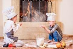 Δύο αμφιθαλείς - αγόρι και κορίτσι - στα καπέλα αρχιμαγείρων ` s κοντά στη συνεδρίαση εστιών στο πάτωμα κουζινών που λερώνεται με Στοκ Φωτογραφίες