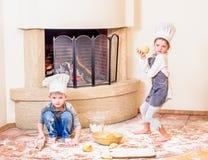 Δύο αμφιθαλείς - αγόρι και κορίτσι - στα καπέλα αρχιμαγείρων ` s κοντά στη συνεδρίαση εστιών στο πάτωμα κουζινών που λερώνεται με Στοκ φωτογραφία με δικαίωμα ελεύθερης χρήσης