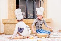 Δύο αμφιθαλείς - αγόρι και κορίτσι - στα καπέλα αρχιμαγείρων ` s κοντά στη συνεδρίαση εστιών στο πάτωμα κουζινών που λερώνεται με Στοκ Φωτογραφία