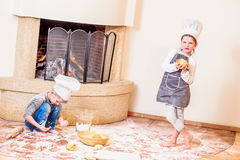 Δύο αμφιθαλείς - αγόρι και κορίτσι - στα καπέλα αρχιμαγείρων ` s κοντά στη συνεδρίαση εστιών στο πάτωμα κουζινών που λερώνεται με Στοκ εικόνα με δικαίωμα ελεύθερης χρήσης