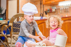 Δύο αμφιθαλείς - αγόρι και κορίτσι - στα καπέλα αρχιμαγείρων ` s που κάθονται στο πάτωμα κουζινών που λερώνεται με το αλεύρι, παί Στοκ Εικόνα