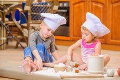 Δύο αμφιθαλείς - αγόρι και κορίτσι - στα καπέλα αρχιμαγείρων ` s που κάθονται στο πάτωμα κουζινών που λερώνεται με το αλεύρι, παί Στοκ εικόνες με δικαίωμα ελεύθερης χρήσης