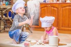 Δύο αμφιθαλείς - αγόρι και κορίτσι - στα καπέλα αρχιμαγείρων ` s που κάθονται στο πάτωμα κουζινών που λερώνεται με το αλεύρι, παί Στοκ εικόνα με δικαίωμα ελεύθερης χρήσης