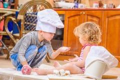 Δύο αμφιθαλείς - αγόρι και κορίτσι - στα καπέλα αρχιμαγείρων ` s που κάθονται στο πάτωμα κουζινών που λερώνεται με το αλεύρι, παί Στοκ φωτογραφίες με δικαίωμα ελεύθερης χρήσης