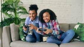 Δύο ανάμιξαν τα σγουρά κορίτσια φυλών που κάθονται στα παιχνίδια στον υπολογιστή κονσολών παιχνιδιού καναπέδων με το gamepad και  Στοκ φωτογραφία με δικαίωμα ελεύθερης χρήσης