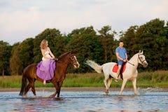 Δύο αναβάτες στην πλάτη αλόγου στο ηλιοβασίλεμα στην παραλία Οι εραστές οδηγούν hors Στοκ Εικόνα