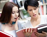 Δύο αναρωτήθηκαν τους σπουδαστές που διαβάστηκαν στη βιβλιοθήκη Στοκ εικόνα με δικαίωμα ελεύθερης χρήσης