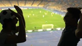 Δύο ανεμιστήρες ποδοσφαίρου δίνουν υψηλός-πέντε μετά από τον αγαπημένο σημειωμένο ομάδα στόχο, συγκινημένες συγκινήσεις φιλμ μικρού μήκους