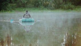Δύο ανθρώπων αλιεία στη λαστιχένια βάρκα στη δασική λίμνη Όμορφο τοπίο, αυγή και ομίχλη πρωινού επάνω από το νερό φιλμ μικρού μήκους