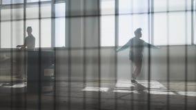 Δύο ανθρώπων οδός που χορεύει μπροστά από το μεγάλο παράθυρο στο εγκαταλειμμένο κτήριο Έφηβοι που κάνουν την κίνηση χορού ταυτόχρ απόθεμα βίντεο