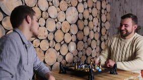 Δύο ανθρώπων παίζοντας το παιχνίδι του σκακιού στον ξύλινο πίνακα και μιλώντας ο ένας στον άλλο Χέρια και χαμόγελο κουνημάτων απόθεμα βίντεο