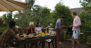 Δύο ανθρώπων παίρνοντας τρόφιμα από τους ανθρώπους σχαρών που κάθονται συλλογή ομάδας επιτραπέζιων στη νέα φίλων στο θερινό πεζού φιλμ μικρού μήκους