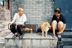 Δύο ανθρώπων παιχνίδι με ένα σκυλί έξω από το σπίτι τους σε μια πόλη παραδοσιακού κινέζικου hutong στοκ φωτογραφία με δικαίωμα ελεύθερης χρήσης