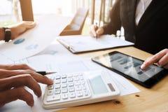 Δύο ανώτατα στελέχη επιχείρησης που συζητούν τα έγγραφα στοιχείων του χρηματιστηρίου στο σύγχρονο γραφείο στοκ εικόνα