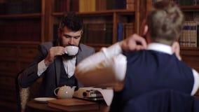 Δύο αξιοσέβαστα και ευφυή άτομα επικοινωνούν στη βιβλιοθήκη Η έννοια της επικοινωνίας Δύο άτομα πίνουν τον καφέ και απόθεμα βίντεο
