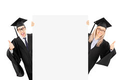 Δύο απόφοιτοι φοιτητές που στέκονται πίσω από την επιτροπή και που δίνουν φυλλομετρούν επάνω Στοκ Εικόνα