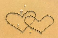 Δύο από τις καρδιές που επισύρονται την προσοχή σε μια αμμώδη παραλία θάλασσας Αγάπη Στοκ Εικόνα