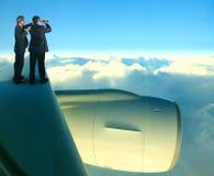 Δύο από το ασιατικό επιχειρησιακό άτομο που στέκεται στο φτερό αεροπλάνων αεριωθούμενων αεροπλάνων πέρα από το λευκό Στοκ φωτογραφίες με δικαίωμα ελεύθερης χρήσης