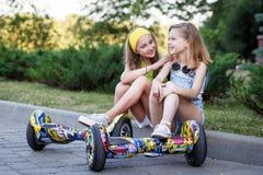 Δύο αρκετά ευτυχή κορίτσια που στηρίζονται με τα hoveboards στοκ φωτογραφία