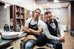 Δύο αρσενικά haidressers και hairstylists που κάθονται στο κατάστημα κουρέων στοκ φωτογραφία με δικαίωμα ελεύθερης χρήσης